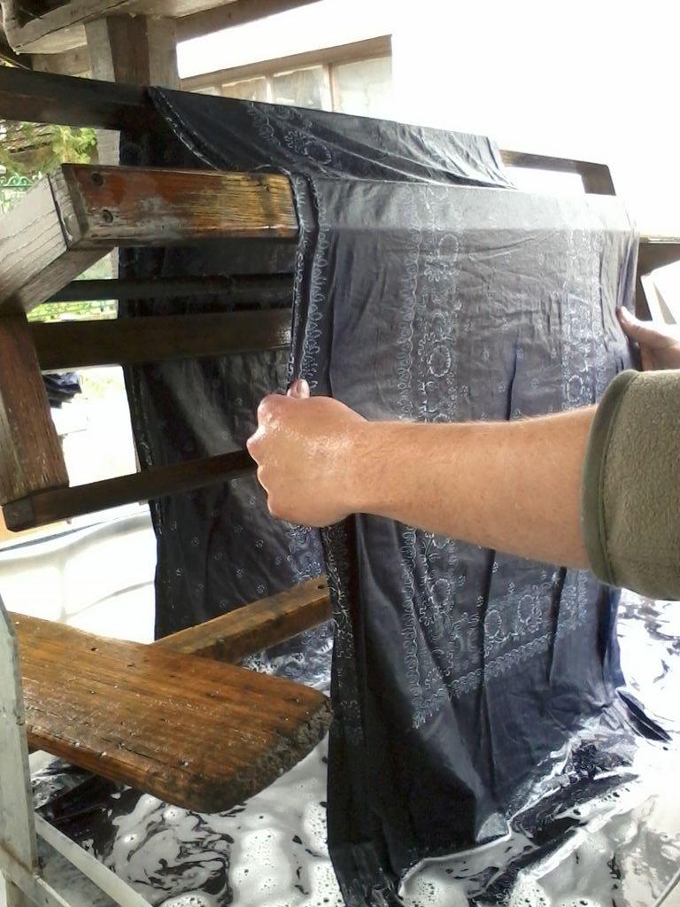 """Der Stoff wird in einen grossen Waschbottich mit Essigwasser gelegt. Es wird der """"Papp"""" komplett aus dem Stoff gewascht, langsamm wird das weisse Muster sichtbar."""