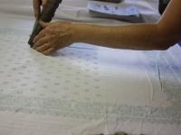 """Ein wachsähnlicher, aufgrund einer alten Rezeptur hergestellter Stoff (der sogenannte """"Papp"""") wird mit Holzmodeln auf das weiße Stoffe aufgebracht."""