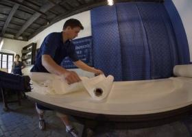"""Der Stoff wird von den (ca. 100 Meter langen) großen Rollen abgerollt und in 25-30 Meter lange Teile geschnitten, und damit zum Auskochen vorbereitet (der Stoff wird schön zusammengelegt). Das nennt man """"Laufen""""."""