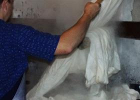 """Die weiße Stoffstücke werden in unserer """"Hexenküche"""" in riesengroßen Kupferkesseln im heißen, Seifenwasser eine Stunde lang gekocht, damit die infolge des Webens entstandenen Verschmutzungen entfernt werden."""