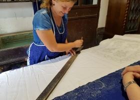 Vor dem Aufdruck mit der Hand werden die Stellen der Muster auf dem weißen Stoff markiert, damit das Aufsetzen der kleineren Muster einfacher wird.